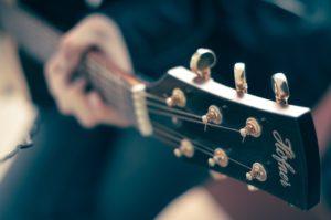 main gauche sur manche guitare folk