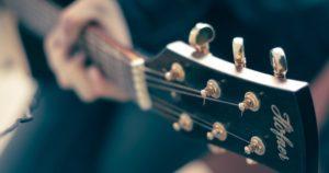 main gauche sur manche guitare flouté